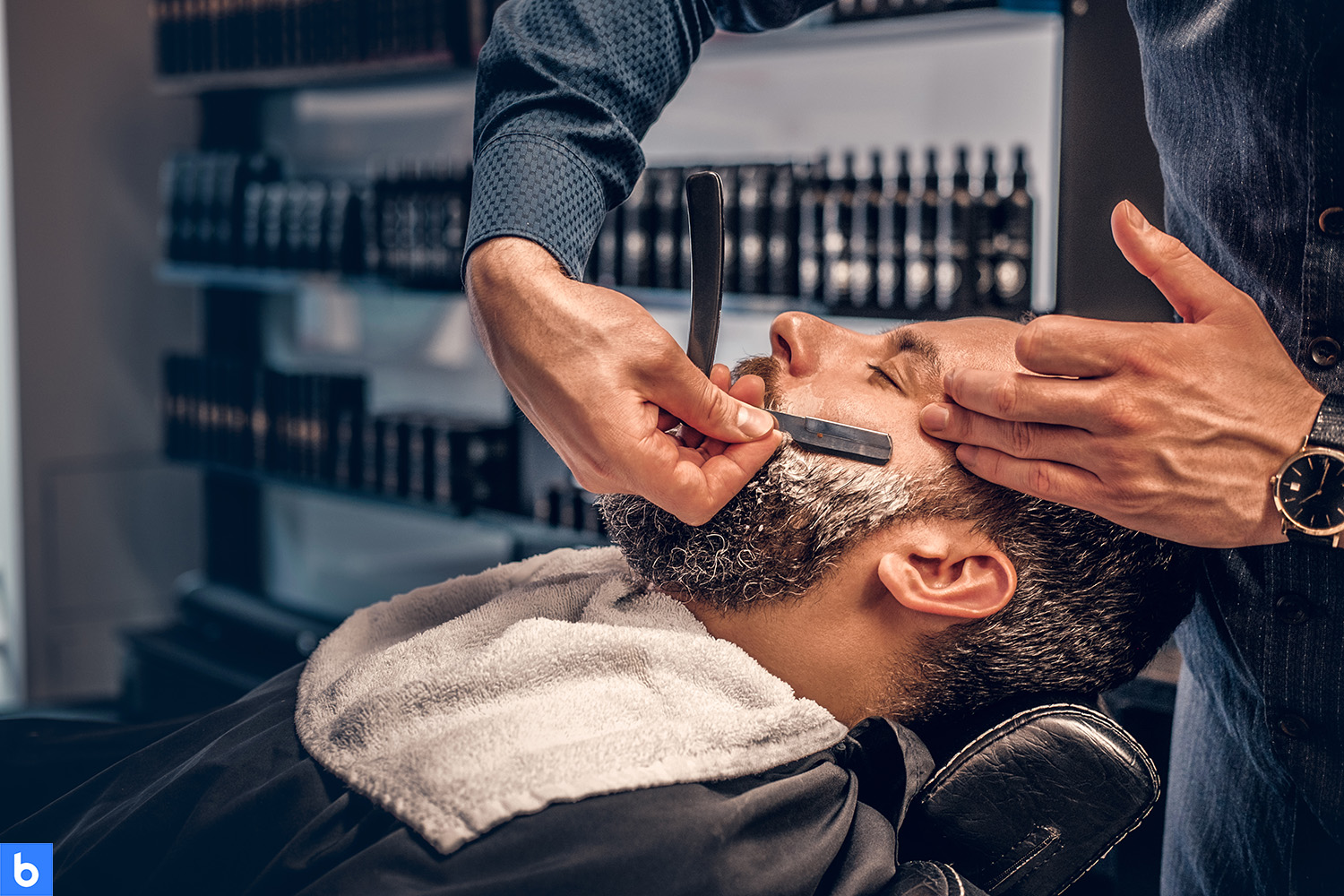 This is the cover for our Best Straight Razor article. It features a man sitting in a barber shop being shaved with a straight razor. The background looks like a barber shop, but out of focus in the image.