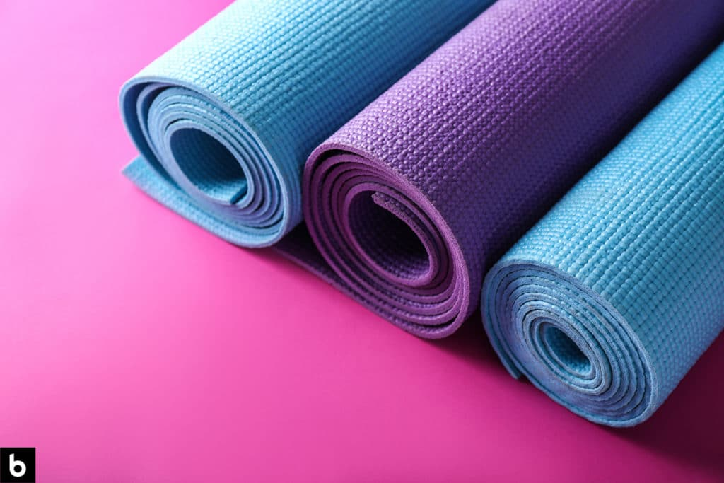 This is an image of 3 rolled up yoga mats on a pink background.