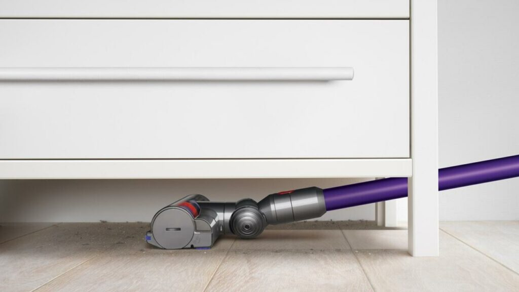 This is an image of a Dyson vacuum cleaner vacuuming under a storage shelf.