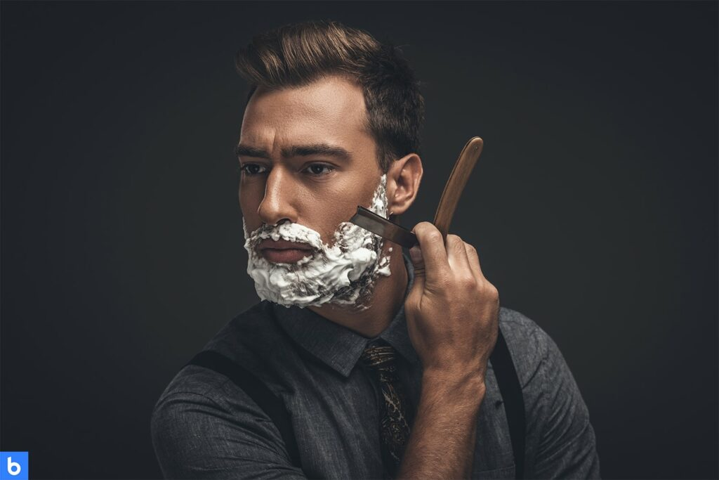 This is a cover photo for the Best Straight Razor 2021 Buying Guide. It is a photo of a man using shaving cream and a straight razor to shave. He is dressed in a slate grey shirt with a tie and suspenders, with a dark black background behind him.