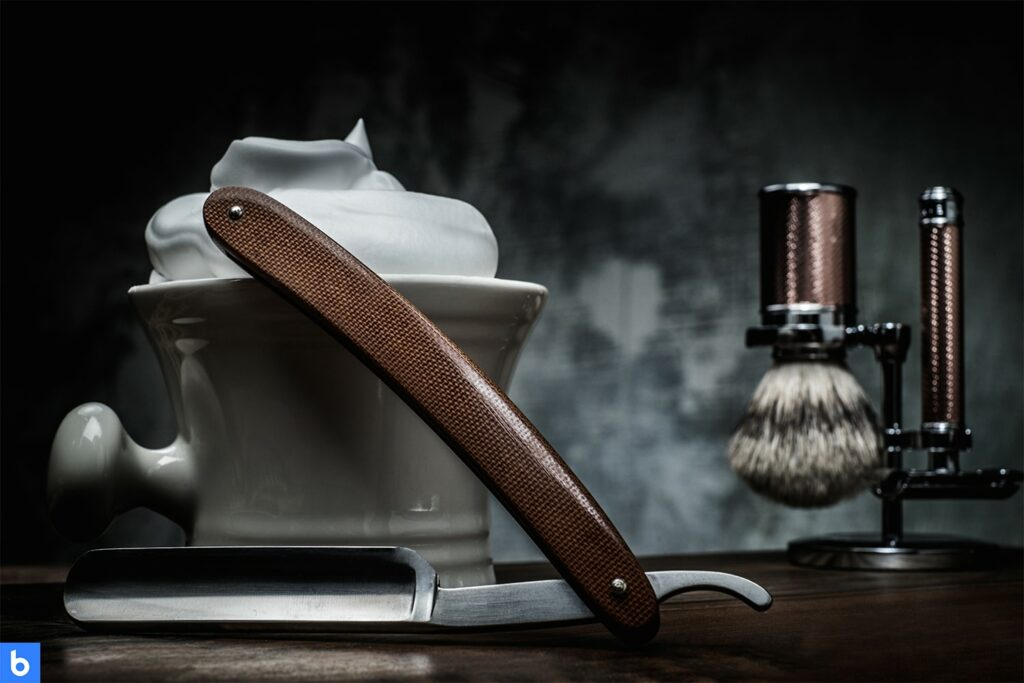 This is a photo of a shaving kit placed on a table. It includes shaving cream, an application brush, and a straight razor.