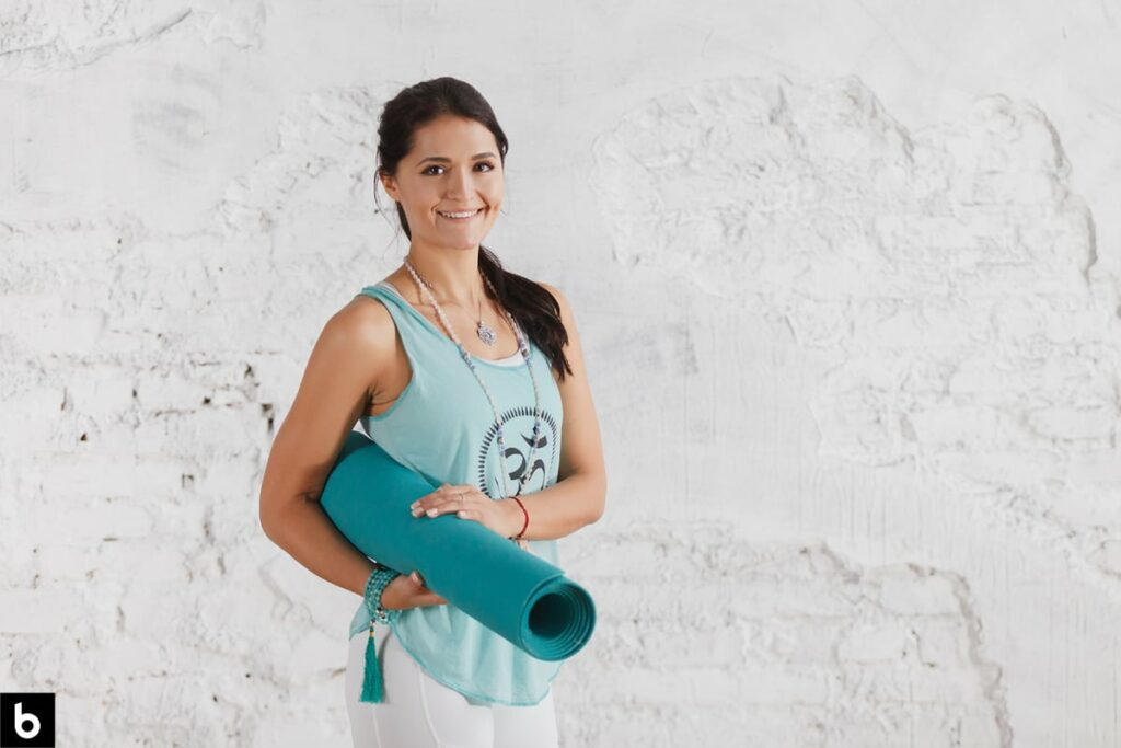 This is an image of a woman holding a yoga mat, dressed in workout apparel.