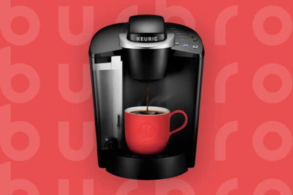 This is the cover photo in our Best Keurig Coffee Maker article. It features a black and silver Keurig machine overlaying a cherry red poster background with an embossed Burbro logo.