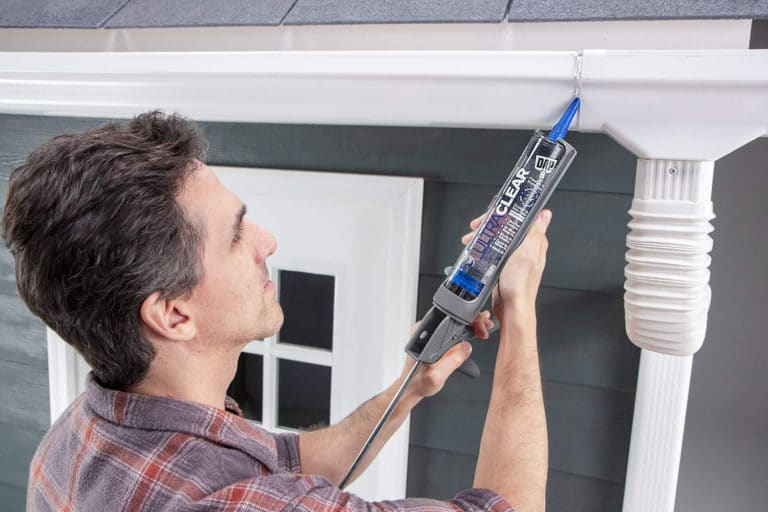 This is the cover photo for our Best Caulking & Sealants article. It shows a man using a caulking gun to seal a gutter.