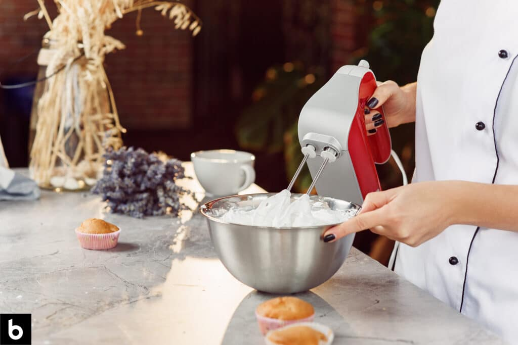 This is a photo for the Best Hand Mixer 2021 article. Woman mixing whipped cream in a mixing bowl with a hand mixer. There are several muffins sitting on the counter in the background.