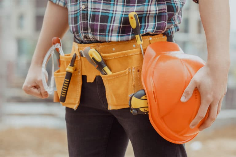 This is the cover photo for our Best Tool Belt article. It shows a construction worker wearing black pants and a plaid shirt wearing a tool belt with assorted tools inside. There is a blurred out background of the construction site.