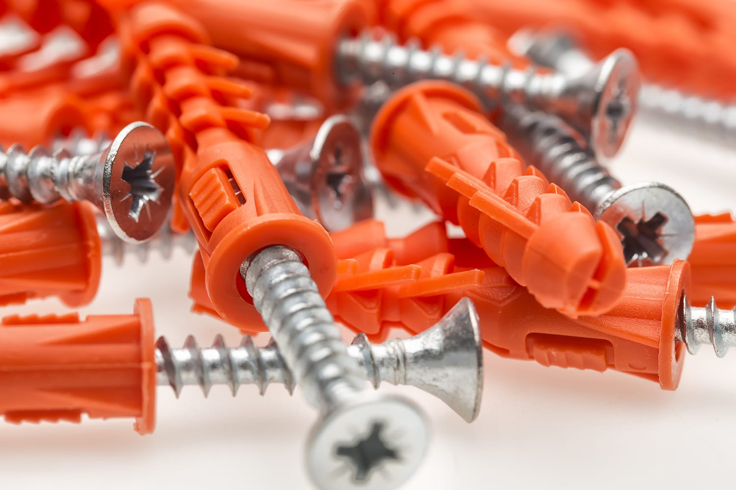 This is a cover photo for our Best Wall Anchors article. It features a pile of orange wall anchors with preset screws inserted.