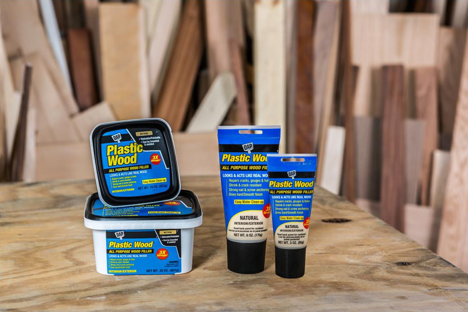 This is the cover photo for our Best Wood Filler article. It shows several tubes and buckets of wood filler on top of a wooden table and various wood scraps in the background.