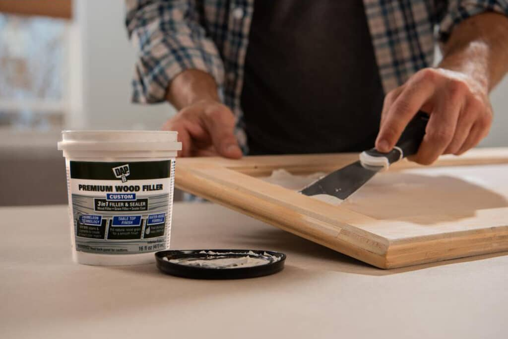 This is a cover photo for our Wood Filler Buying Guide 2021. It shows a person applying wood filler to a cabinet door with a spatula. They are wearing a plaid shirt and there is a bucket of wood filler placed on the table. There is a blurry garage background behind the person.