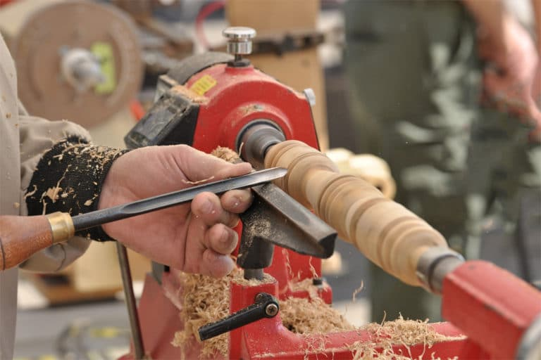 This is the cover photo for our Best Wood Lathe article. It shows a person using a wood lathe to shave and shape a wood dowel. There are wood shavings flying all over, and a blurred background with various tools in the peripheral.