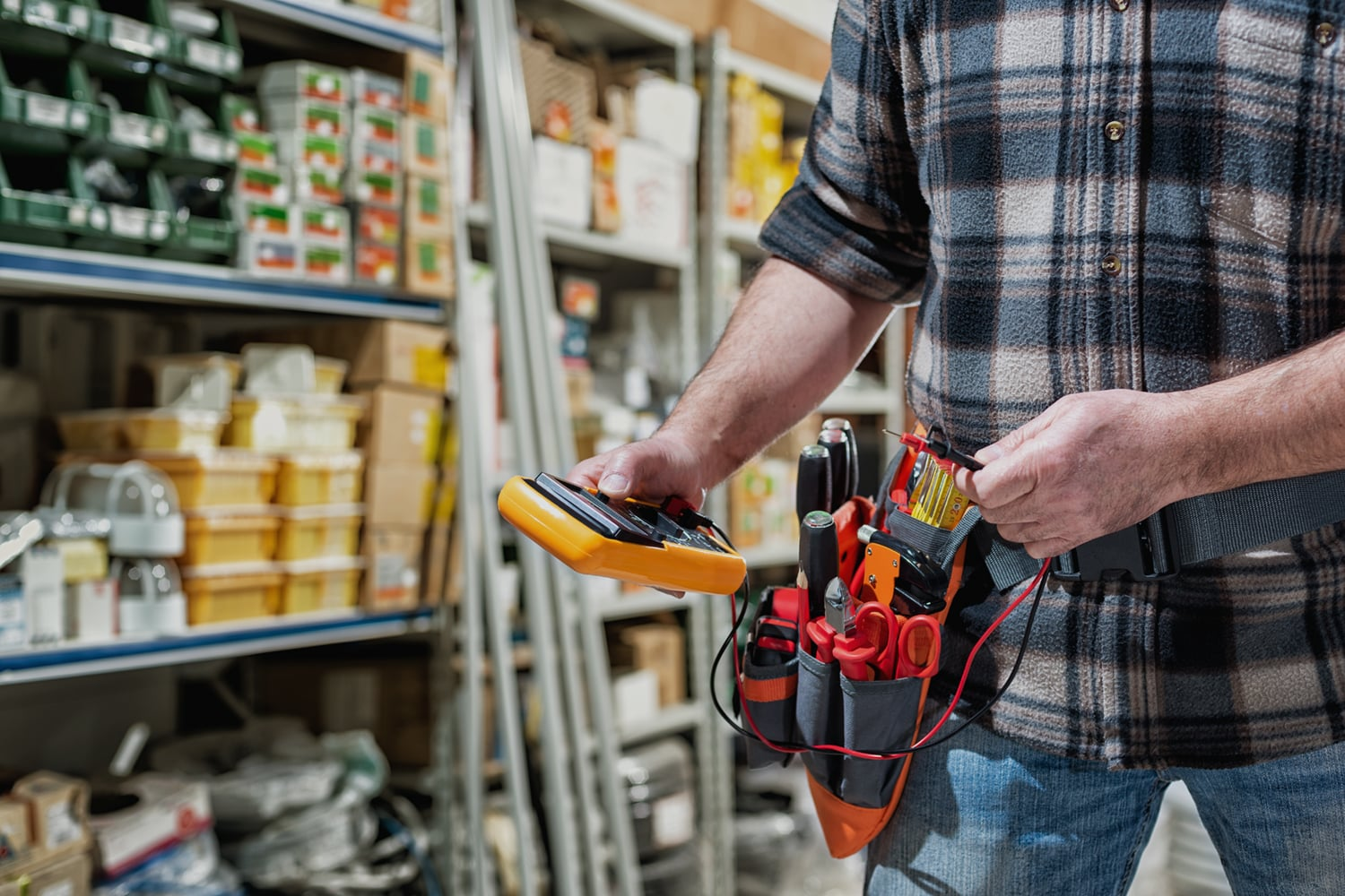 This is the cover photo for our Best Electrician Tool Belt article. It shows an electrician in a store isle, holding a multimeter, wearing a tool belt with tools inside. The background has several shelves of supplies.