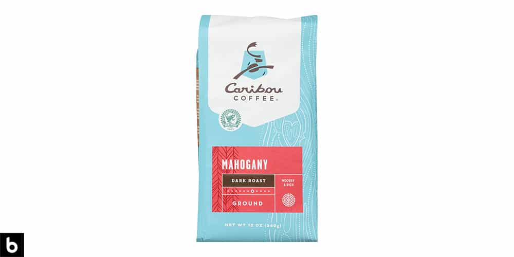 This is a product image of a blue and red bag of Caribou Coffee Mahogany Dark Roast ground coffee.