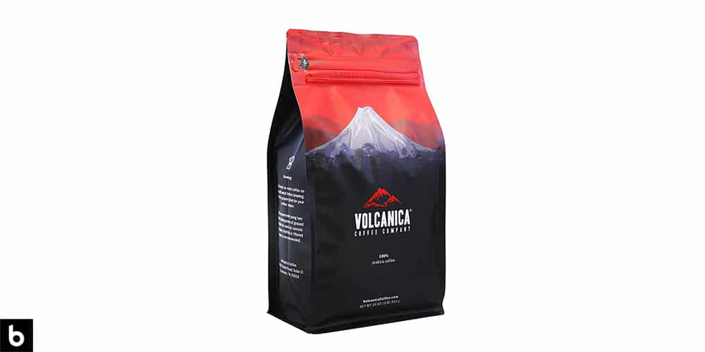 This is a product image of a red and navy Volcanica Coffee Company medium roast coffee beans.