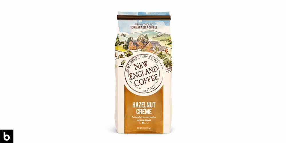 This is a product image for our Best Flavored Coffee 2021 article. It features a blue and gold colored bag of New England Hazelnut Crème coffee beans. There is a watercolor painting of a countryside on the side of the bag.