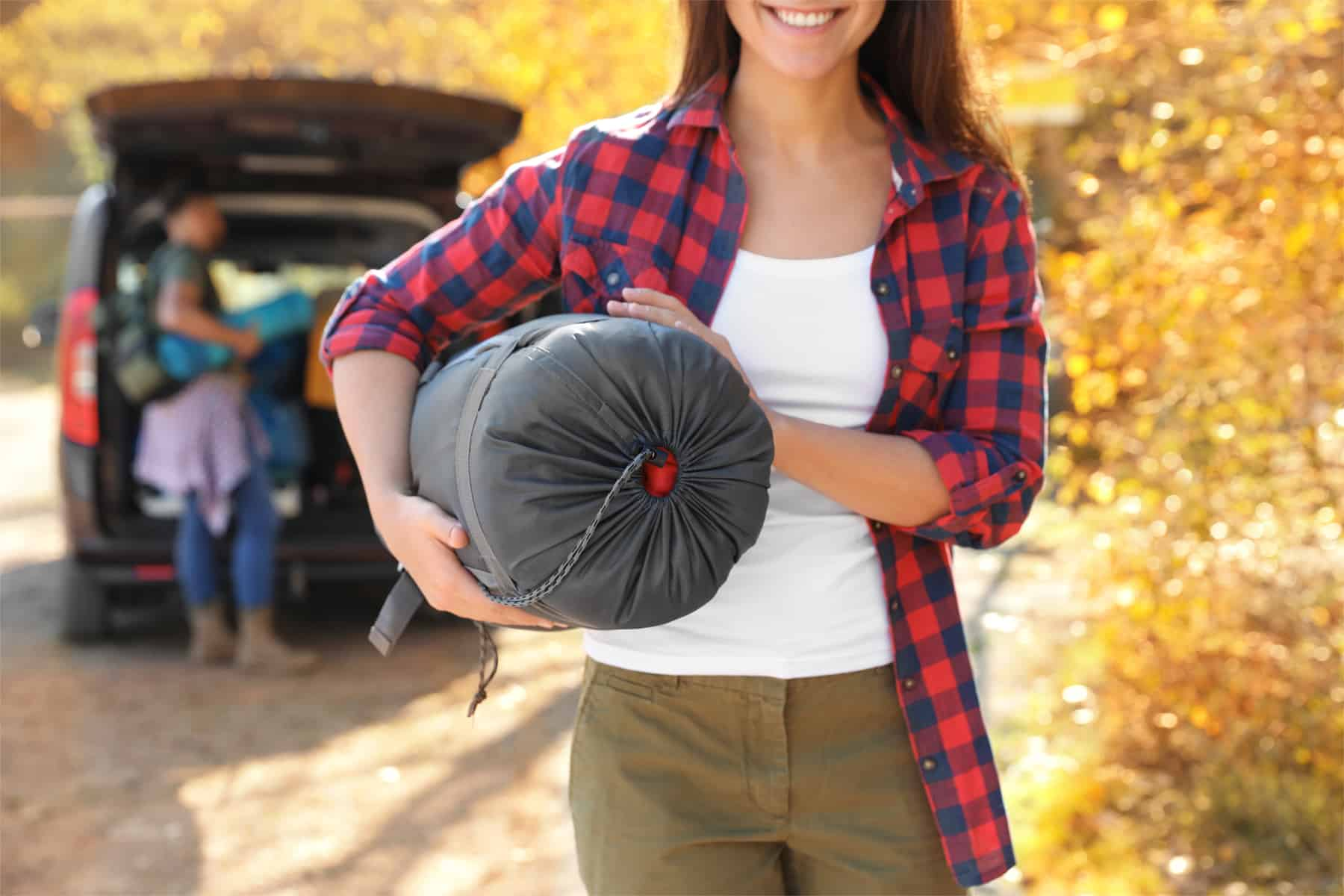This is the cover photo for our Best Sleeping Bag for Camping article. It features a woman holdings a sleeping bag with a man loading a vehicle in the background.